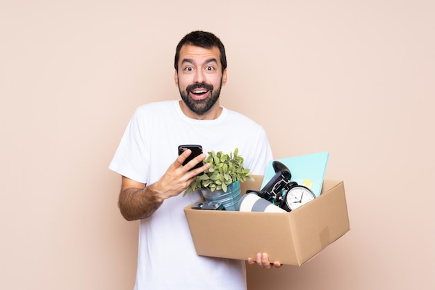Mens die een doos houdt en zich in nieuw huis over geïsoleerde muur beweegt verrast en een bericht verzendt
