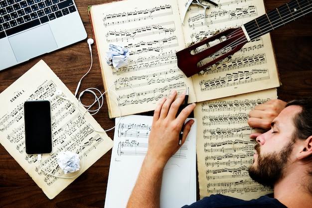 Mens die een dutje neemt terwijl het werken aan muziek