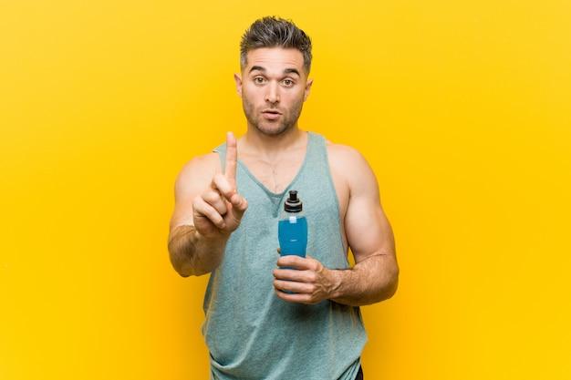 Mens die een energiedrank houdt die nummer één met vinger toont