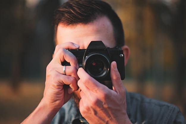 Mens die een foto met een uitstekende camera neemt. portret van een fotograaf in een herfst buitenomgeving