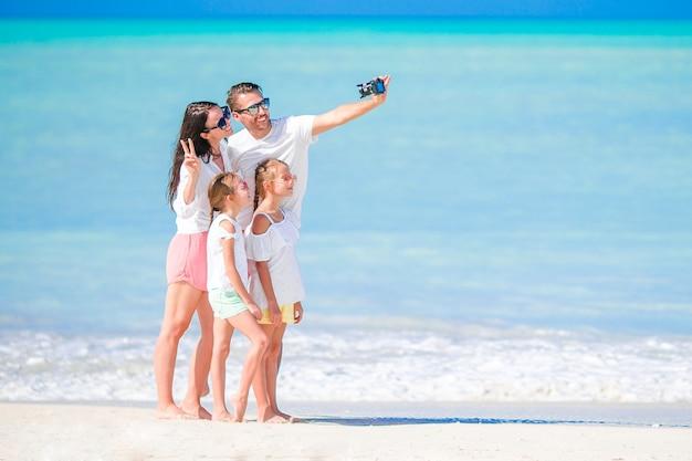 Mens die een foto van zijn familie op het strand neemt. familie vakantie
