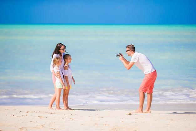 Mens die een foto van zijn familie op het strand neemt