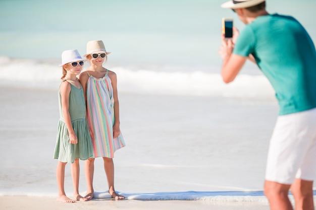 Mens die een foto van zijn kinderen op het strand neemt