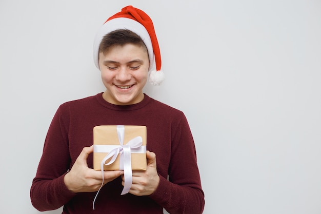 Mens die een gift voor iemand aanbiedt of toont. gelukkig jonge hipster met een geschenk in handen.