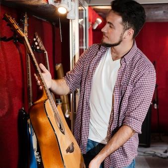 Mens die een gitaar kiest uit een stapel in de studio