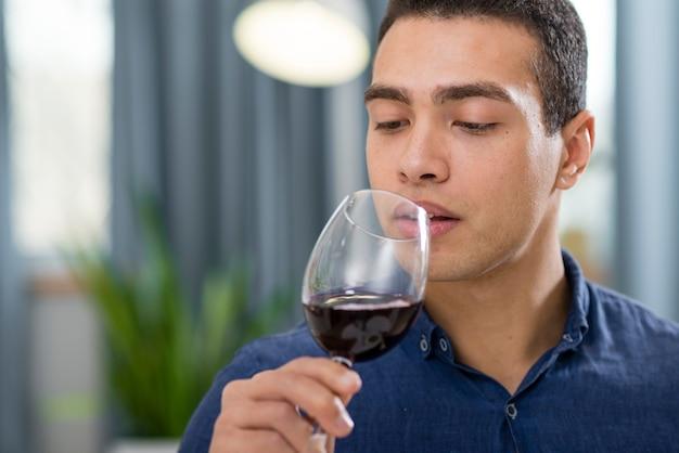 Mens die een glas rode wijn met exemplaarruimte houdt