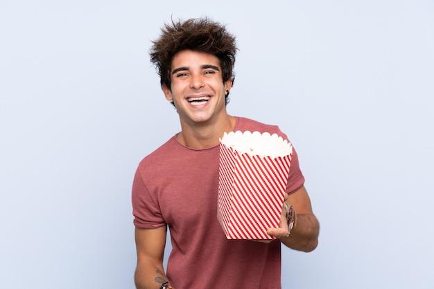 Mens die een grote kom popcorns over geïsoleerde muur houdt