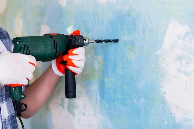 Mens die een hamerboor op een muur houdt