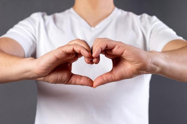 Mens die een hartvorm met zijn geïsoleerde handen maakt