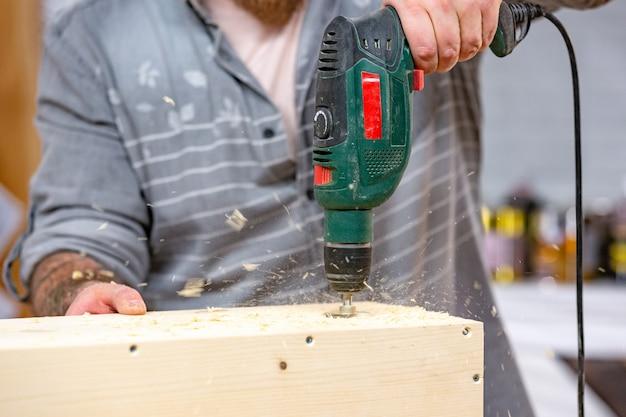 Mens die een houten plankenclose-up boren