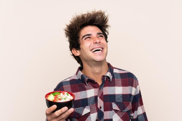Mens die een komhoogtepunt van noedels houdt omhoog kijkend terwijl het glimlachen