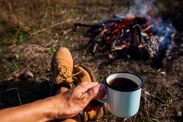 Mens die een kop van koffie naast een kampvuur houdt