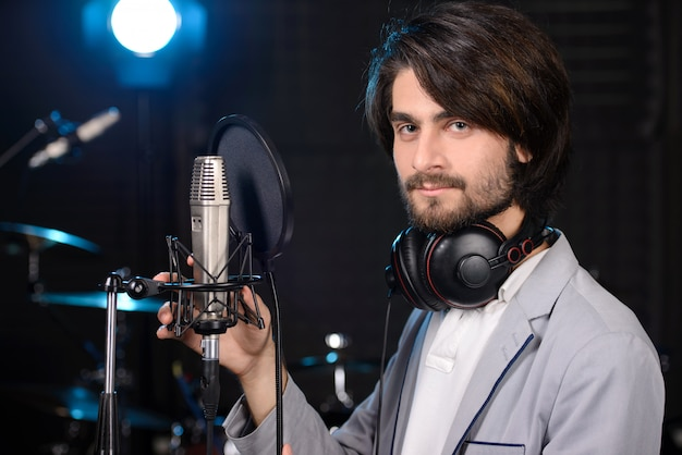 Mens die een lied in een professionele studio opneemt.
