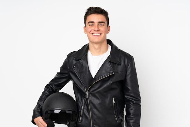 Mens die een motorfietshelm houden die bij het witte muur lachen wordt geïsoleerd