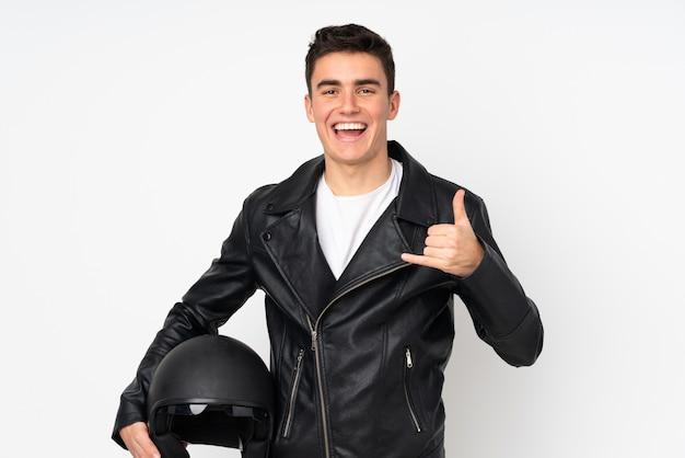 Mens die een motorfietshelm houdt die op witte muur wordt geïsoleerd die telefoongebaar maakt