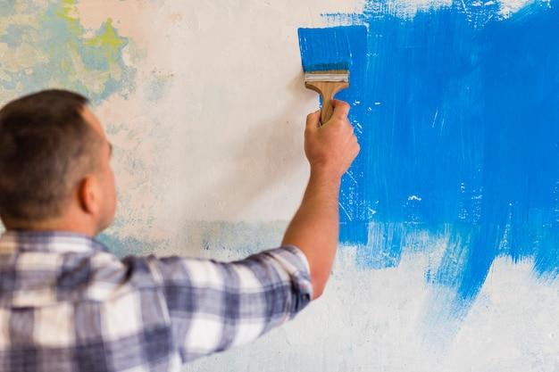 Mens die een muur met blauwe verf schildert