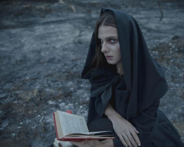 Mens die een open boek houdt en camera bekijkt