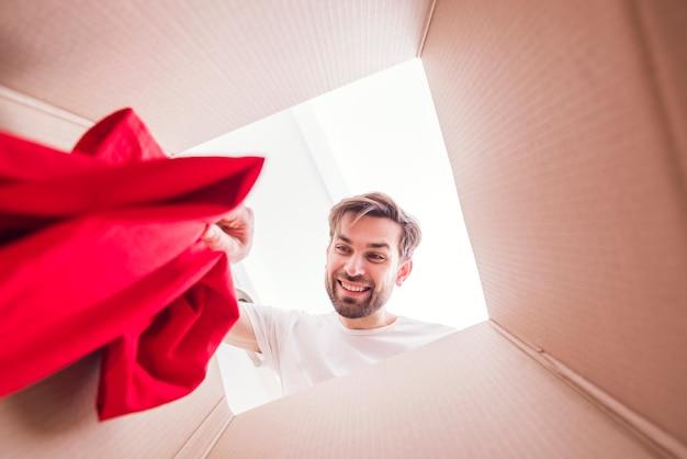 Mens die een overhemd binnen bodem van de doosmening houdt