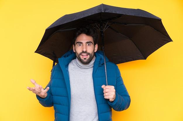 Mens die een paraplu over geïsoleerde muur houdt