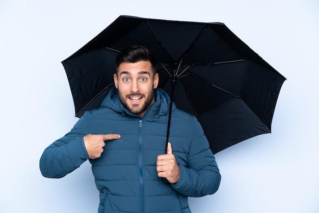 Mens die een paraplu over geïsoleerde muur met verrassingsgelaatsuitdrukking houdt