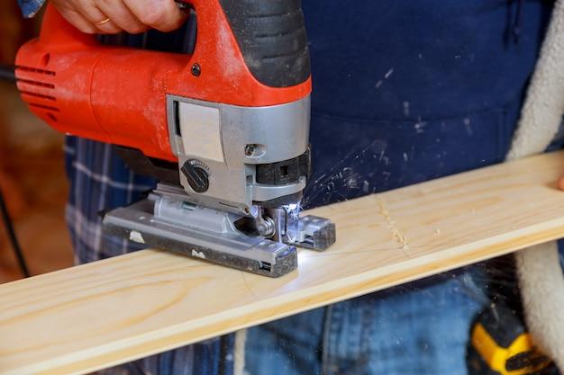 Mens die een plank met een figuurzaagmachine snijdt die houten raad zaagt