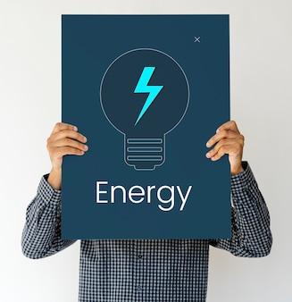 Mens die een raad met het concept van de energie houdt