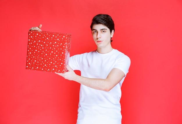 Mens die een rode giftdoos in valentijnskaartdag aanbiedt