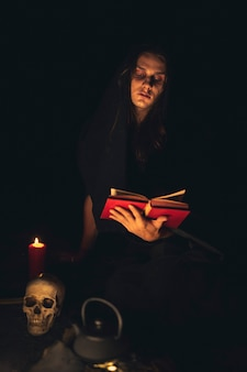 Mens die een rood spreukboek leest in dark