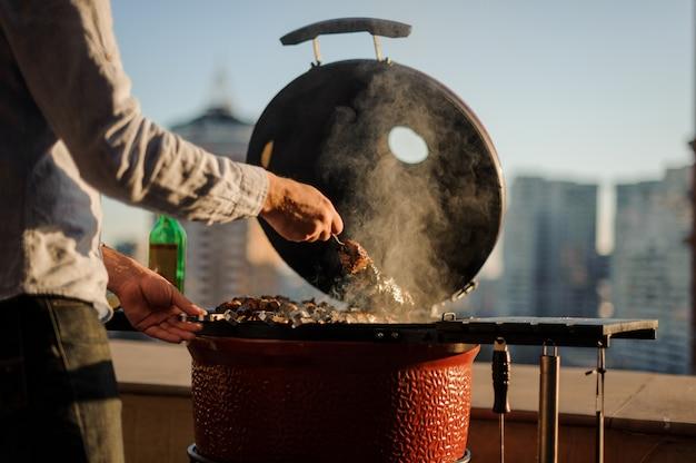 Mens die een schotel in een barbecuegrill kookt die met het koken van hulpmiddelen wordt uitgerust die zich op het dak bevinden