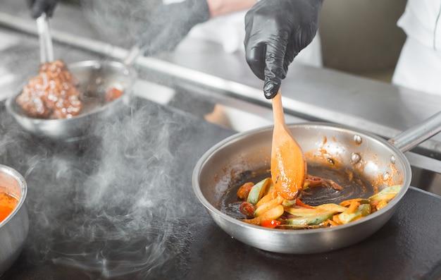 Mens die een schotel in een restaurant kookt