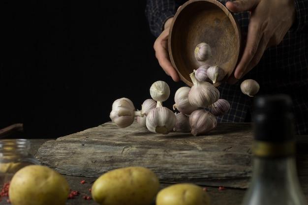 Mens die een schotel met knoflook en aardappels in de keuken op een rustieke houten lijst voorbereiden