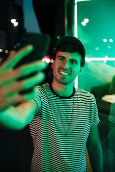 Mens die een selfie en glimlach in de nacht neemt