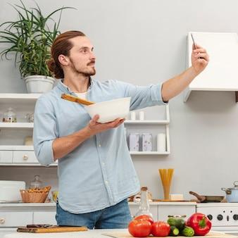 Mens die een selfie met een keukenkom neemt