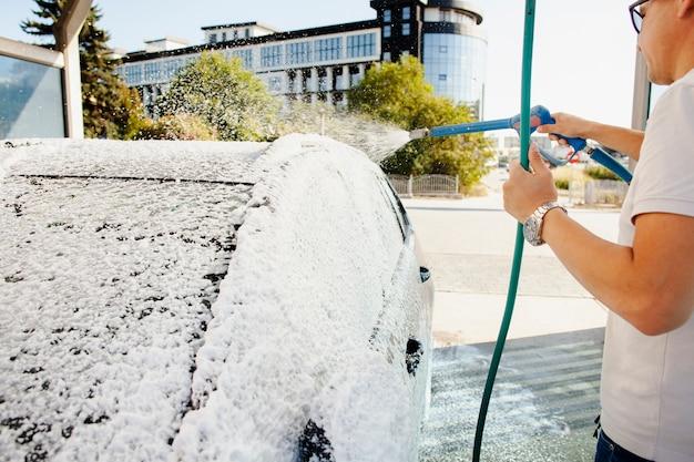 Mens die een slang gebruikt om zijn auto schoon te maken