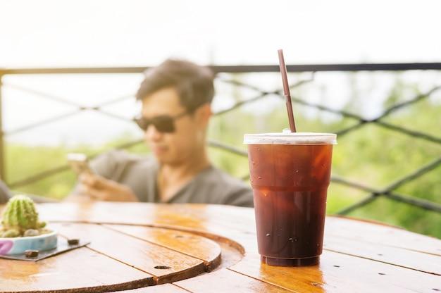 Mens die een smartphone in een koffiewinkel met behulp van.