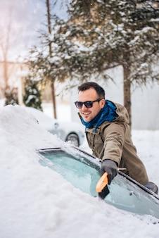 Mens die een sneeuw behandelde auto schoonmaakt