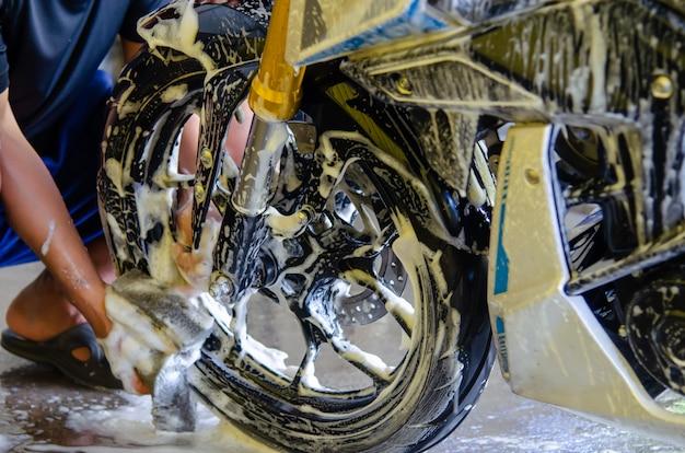 Mens die een spons houdt om de wielenmotorfiets te wassen