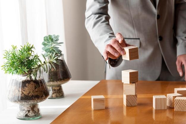 Mens die een stapel van houten dozen bouwt