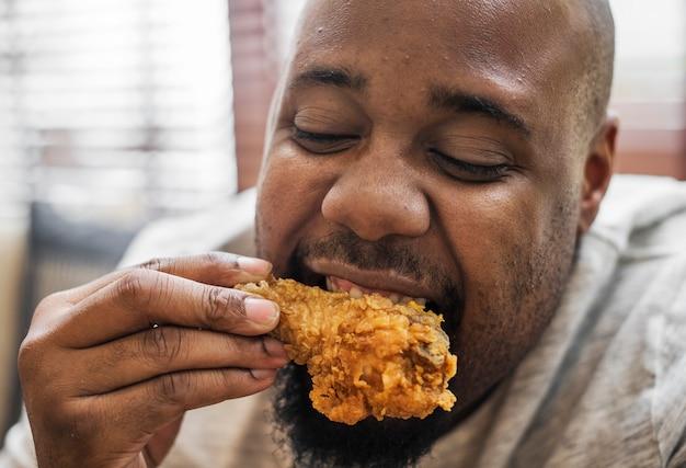 Mens die een stuk gebraden kip eet