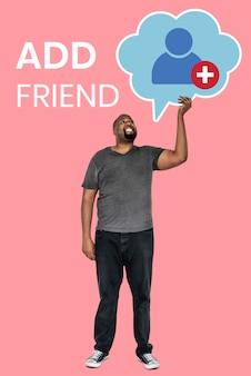Mens die een symbool van het vriendenverzoek voor sociaal netwerk houdt