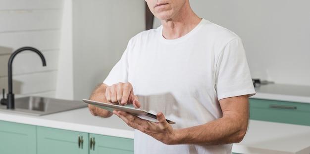 Mens die een tablet thuis gebruikt