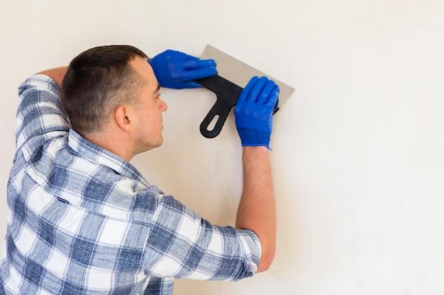 Mens die een troffel houdt terwijl het werken aan muur