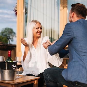 Mens die een verlovingsring toont aan zijn gelukkig meisje in een restaurant