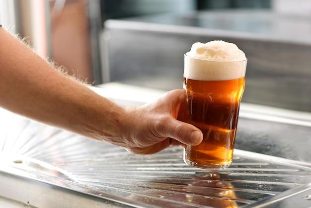 Mens die een vers glas gekoeld bier van het vat houdt