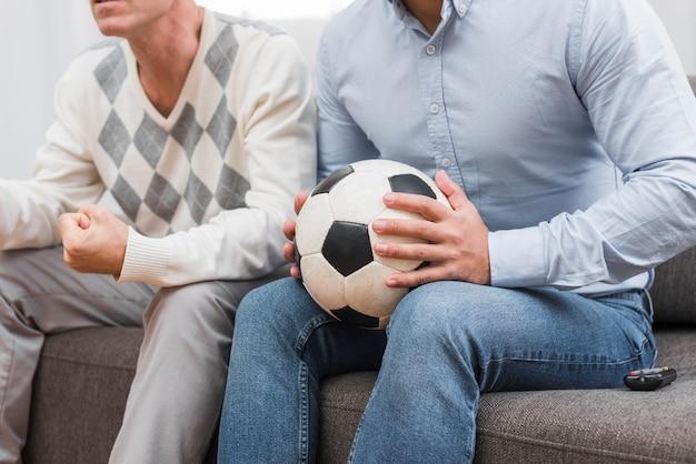 Mens die een voetbal met handen houdt
