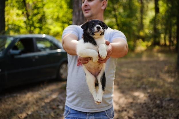Mens die een zwart-wit puppy in het bos houdt