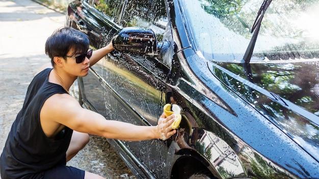 Mens die een zwarte auto wast.