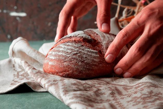 Mens die eigengemaakt tarwebrood met bloem op het op een witte handdoek met twee handen zet.