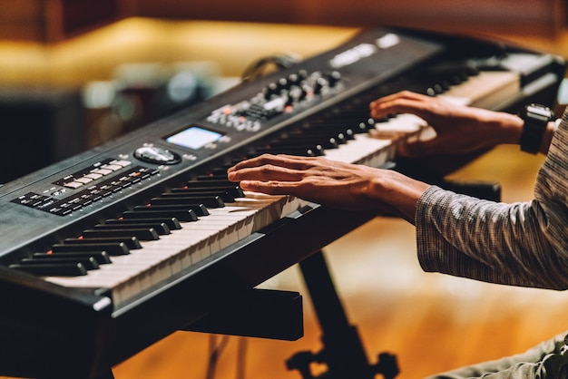Mens die elektronische muzikale toetsenbordsynthesizer speelt