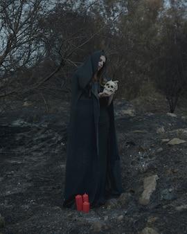 Mens die en een schedel voor halloweenpartij bevinden zich houden